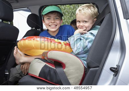 Portrait of three smiling boys in the car