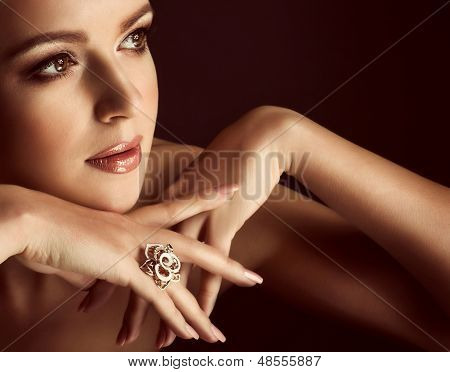 Portrait of beautiful young woman with makeup in luxury jewelry