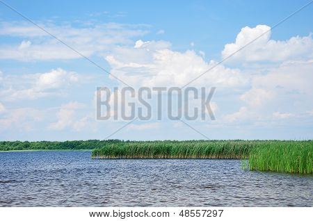 Sky With Fluffy Clouds Above A Lake