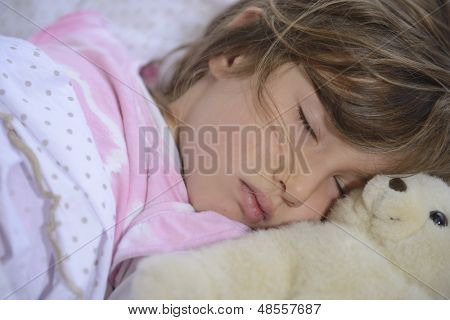 cute girl sleeping in bed with teddy bear