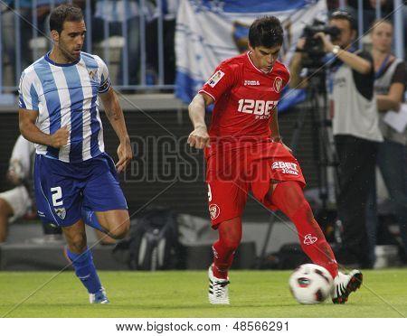 MALAGA, SPAIN. 19/09/2010. Jesus G���¡mez the Malaga defender and Diego Perotti a Sevilla midfield player  during the La Liga match between CF Malaga and Sevilla, played in the La Rosaleda Stadium
