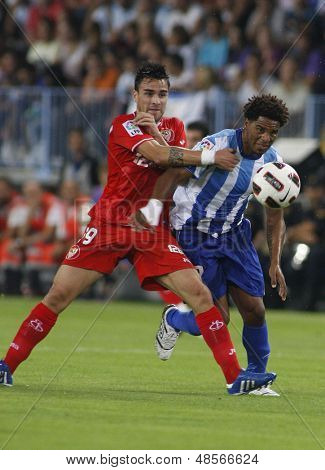 MALAGA, SPAIN. 19/09/2010.  Luca Cigarini a Sevilla midfield player fouls Eliseu the Malaga midfielder during the La Liga match between CF Malaga and Sevilla, played in the La Rosaleda Stadium