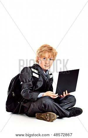 Serious schoolboy sitting with his laptop. Isolated over white.