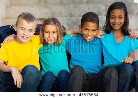 beautiful elementary school students sitting outdoors