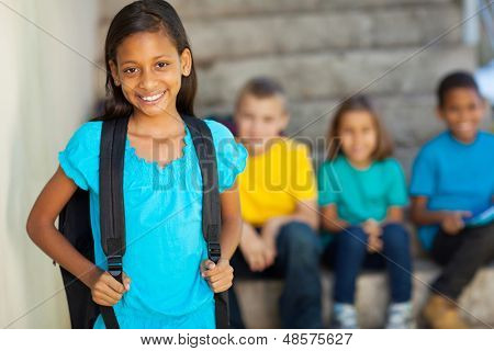 portrait of beautiful elementary school girl with schoolmates on background