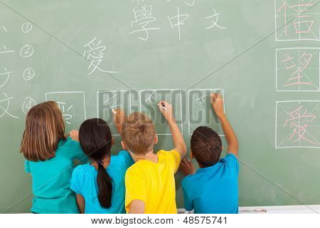 rear view of elementary school students learning chinese writing on chalkboard