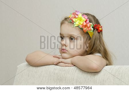 Portrait of a girl that looks thoughtfully left leaning his elbow on the back of the sofa