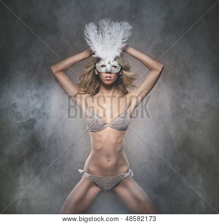 Attractive young lady in mask is dancing striptease over smoky background