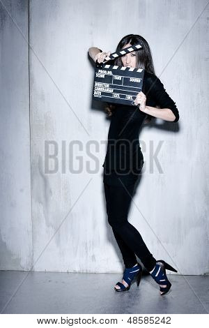 Sensuality beautiful woman with long hairholding clapperboard