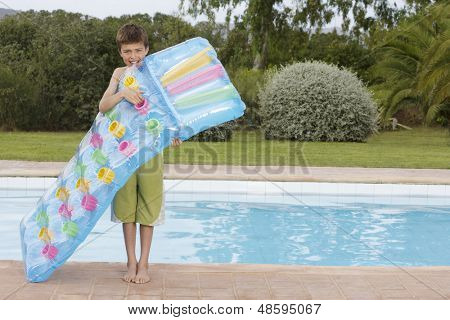 Full length of a young boy blowing up air mattress against the pool