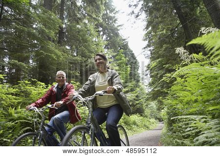Low angle view of mature man and middle aged woman with bikes on forest road
