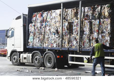 Stacks of recycled paper in lorry at recycling plant