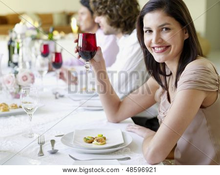 Portrait of beautiful young woman holding wineglass with friends at dinner party