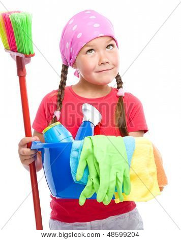 Young girl is dressed as a cleaning maid, holding broom and bucket full of liquids, looking up, isolated over white