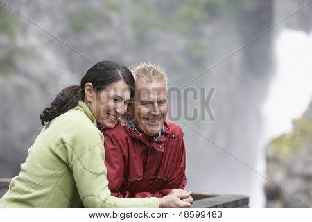 Edad media feliz hombre y una mujer mirando la vista contra un fondo borroso