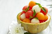 stock photo of cantaloupe  - Fruit salad with melon and watermelon balls in cantaloupe bowl - JPG