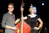 stock photo of bonaparte  - Man in glasses with tambourine and woman in black dress with contrabass in night club - JPG