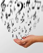 image of musical scale  - a photo of a woman releasing music notes - JPG