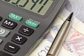 image of irs  - Calculator and pen symbolizing completing your personal Income tax returns for the inland revenue service or IRS - JPG
