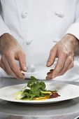 Closeup midsection of a male chef preparing salad in kitchen