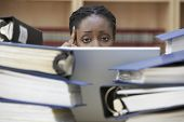 Closeup of a female office worker behind stacks of documents in office