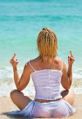 stock photo of middle finger  - Back of woman showing middle finger and enjoying at beach with blue sea on background - JPG