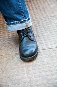 stock photo of skinhead  - Vertical color portrait at an angle of trendy laced up leather boots and stylish turned up denim jeans on a stippled tiled ground - JPG