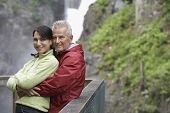 Portrait of a smiling middle aged couple against railing in mountains