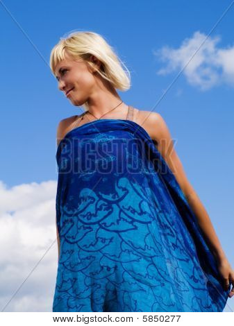 Smiling Blond Woman On The Sunny Blue Sky