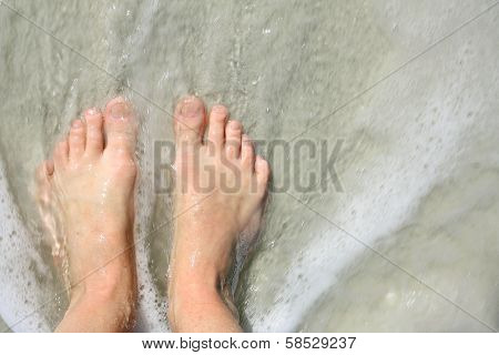Ocean Water Rushing Over Woman's Feet