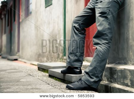 Man's Legs Standing Against The Wall
