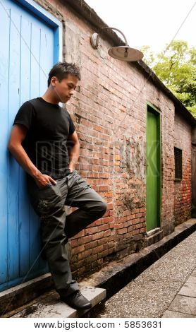 Asian Man Stand Against A Old Door And Lonely