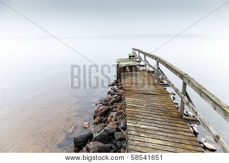 Old Ruined Wooden Pier. Saimaa Lake In Foggy Morning