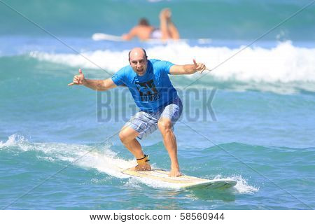 Bald italian man enjoys surfing