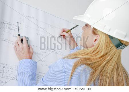 Female Architect Working On Blue Prints