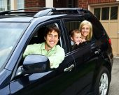 stock photo of happy family  - Happy young family sitting in black car looking out windows - JPG