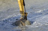 picture of sand gravel  - Excavator bucket dredging sand and gravel from the seafront - JPG