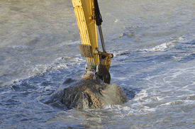 picture of dredge  - Excavator bucket dredging sand and gravel from the seafront - JPG