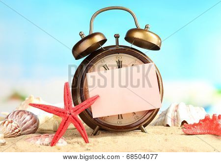 Summertime. Old clock on sand