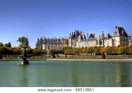 View of the Chateau de Fontainbleu and its reflection across a tranquil lake, situated close to Paris it introduced the Mannerist style of architecture to France and is the largest royal chateau