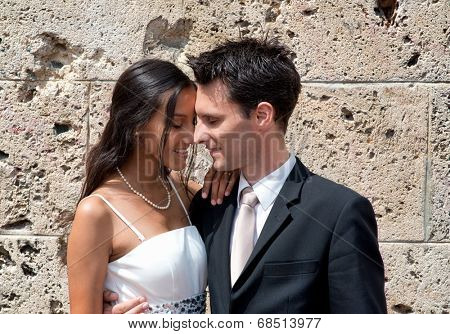 Young man and woman in love sharing a tender moment as they nuzzle heads while standing arm in arm in front of an old stone building