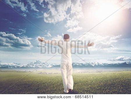 Rear view of a man wearing white summer clothes, with outstretched arms, walking on a green wide meadow towards a snow capped mountain range, under a dramatic bright sunny sky, concept of freedom