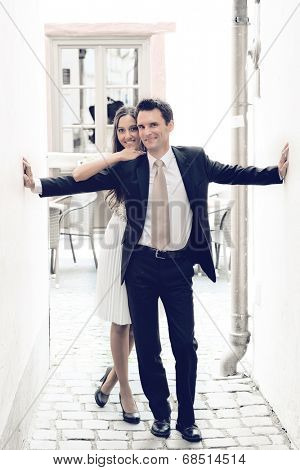 Stylish affectionate young couple posing together in a narrow cobbled walkway between two buildings with the man standing with his arms outstretched with the woman leaning on him from behind