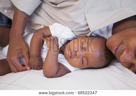 Father napping with baby son on couch at home in the living room