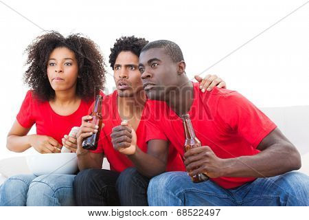Nervous football fans in red on the sofa on white background