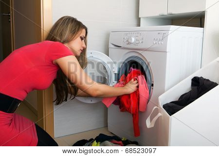 Woman Putting A Cloth Into Washing Machine