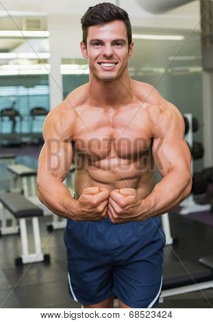 Portrait of a shirtless muscular man flexing muscles in gym