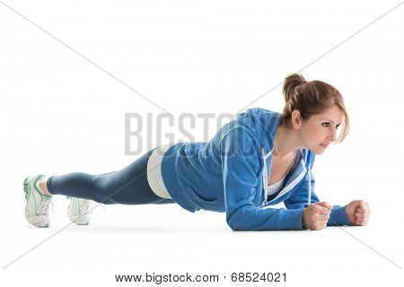 Young woman in basic plank posture over white background