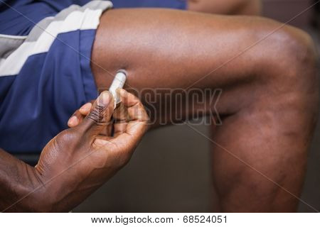 Close up of muscular man injecting steroids in the gym