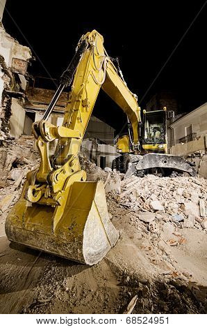 Digger With Mechanical Arm On The Ruins Of A House At Night